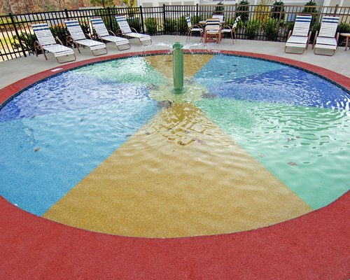 Outdoor swimming pool with fountain and chaise lounge chairs.