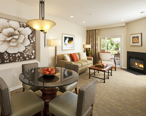 An open plan living and dining area with fire in the fireplace and balcony.