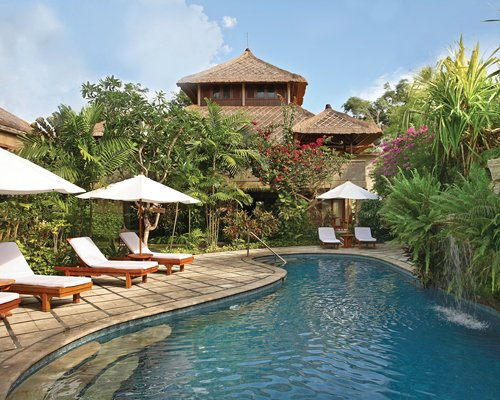 An outdoor swimming pool with chaise lounge chairs and umbrellas alongside the resort.