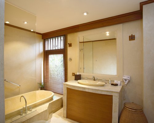 A bathroom with a bathtub and single sink vanity.
