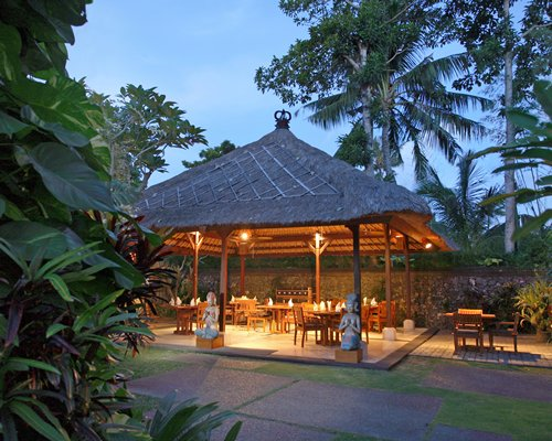 A well furnished outdoor dining area surrounded by trees.