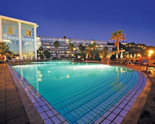 An outdoor swimming pool with chaise lounge chairs alongside multi story resort units at night.