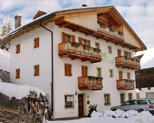 An exterior view of the Bachlaufen Haus resort covered in snow.