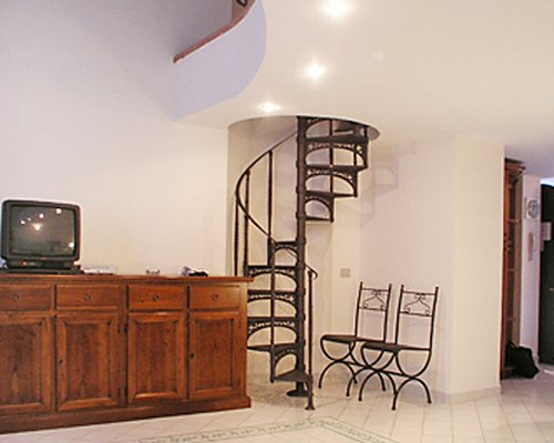 A well furnished indoor room with a spiral staircase and a television.