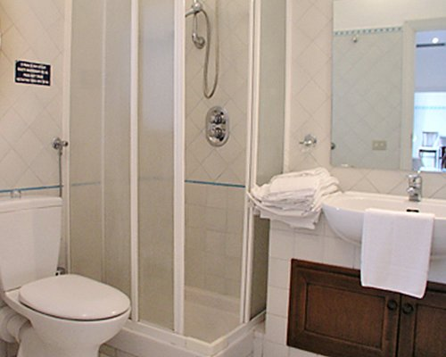 A bathroom with closed sink vanity and shower stall.