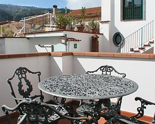 An outdoor dining area in the balcony with the view of resort units.
