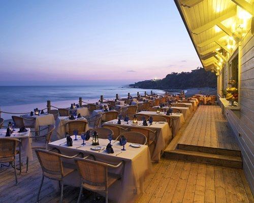 Outdoor restaurant alongside the beach at dusk.