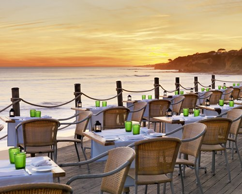 Outdoor restaurant alongside the ocean at dusk.