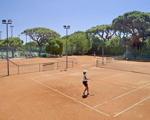 An outdoor tennis court alongside trees.