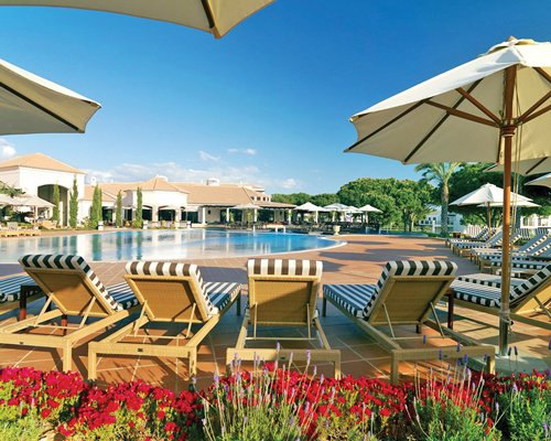 An outdoor swimming pool with chaise lounge chairs alongside multiple resort units.
