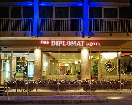 Night view of The Diplomat Club with neon lights.