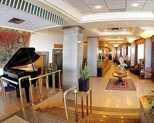 Corridor of The Diplomat Club resort with reception area and piano.