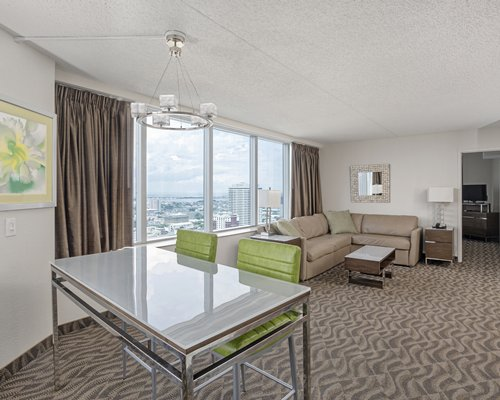 A well furnished living room with a television dining area and ocean view.