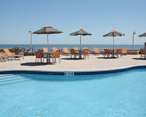 Outdoor swimming pool with chaise lounge chairs alongside the ocean.