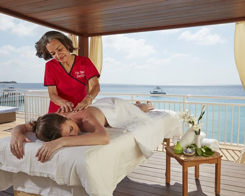 A woman having massage at the spa alongside the sea with boats.
