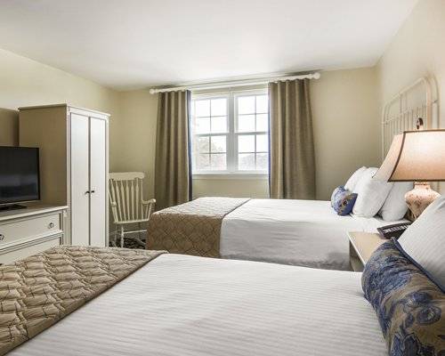 A well furnished bedroom with two beds and television.