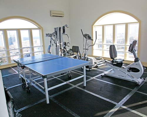 A well equipped fitness center with a ping pong table.