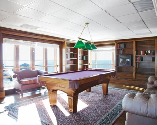 Indoor recreation room with pool table television bookshelf and bay view.