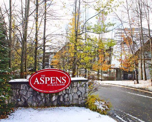 A signboard of the Aspens resort covered in snow.