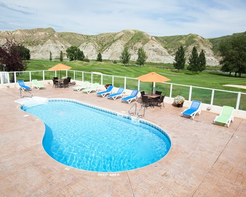 An outdoor swimming pool with chaise lounge chairs patio and sunshades alongside the mountains.