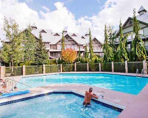 Two outdoor swimming pools with trees alongside resort units.