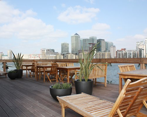 An outdoor dining area with potted plants alongside the waterfront.