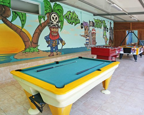 An indoor recreation room with pool tables and table soccer.