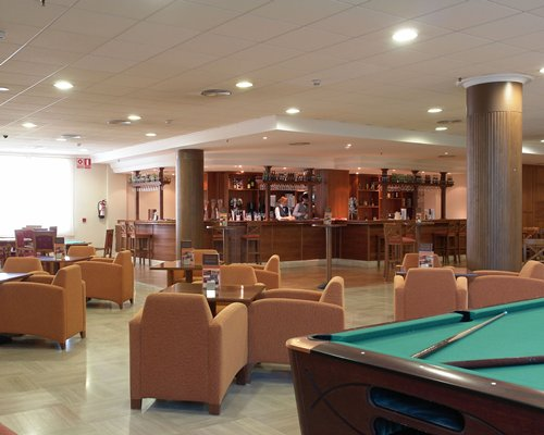 An indoor bar with dining area and pool table.