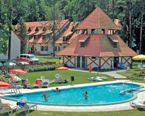 An outdoor swimming pool with chaise lounge chairs alongside the Abbazia Country Club with a parking lot.