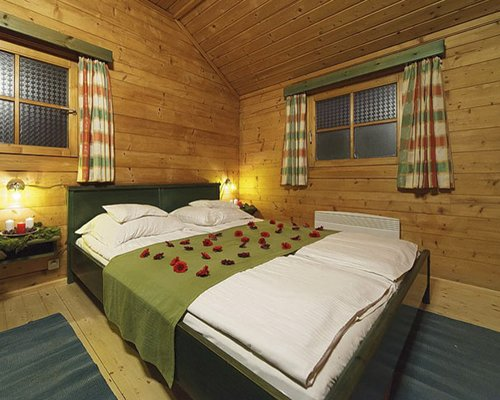A wooden themed bedroom with a double bed.