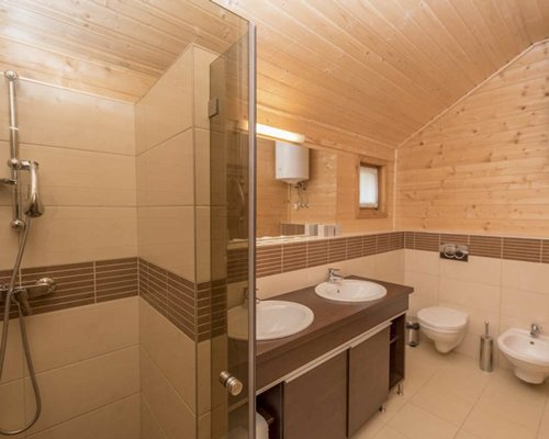 A bathroom with stand up shower and double sink vanity.