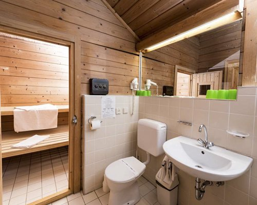 A bathroom with an open sink vanity alongside wooden sauna.