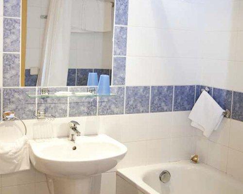 A bathroom with a bathtub and single sink.
