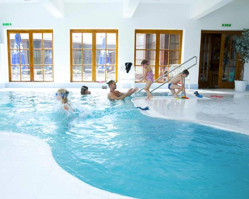 A family enjoying in an indoor swimming pool.