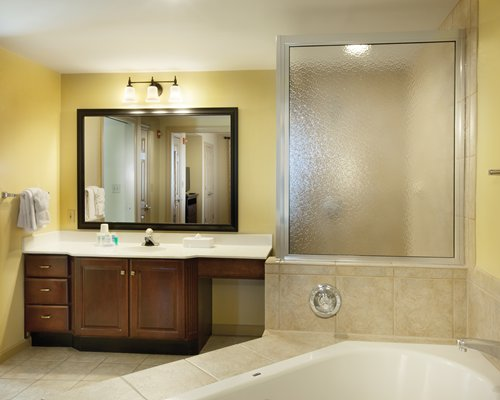 A bathroom with single sink vanity and bathtub.