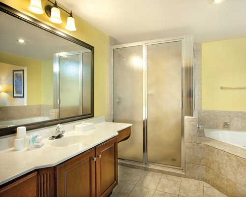 A bathroom with bathtub stand up shower and double sink vanity.
