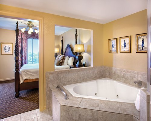 A bathtub alongside a bedroom.