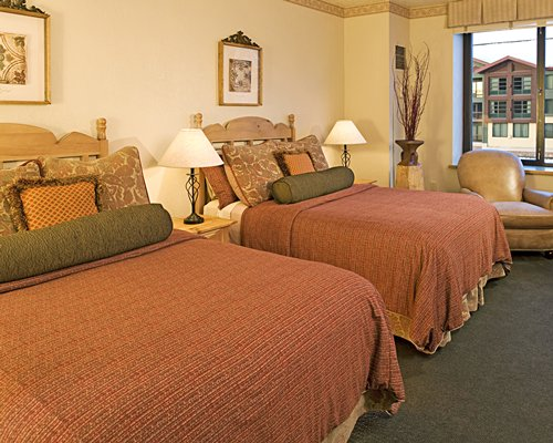 A well furnished bedroom with two beds and a patio.