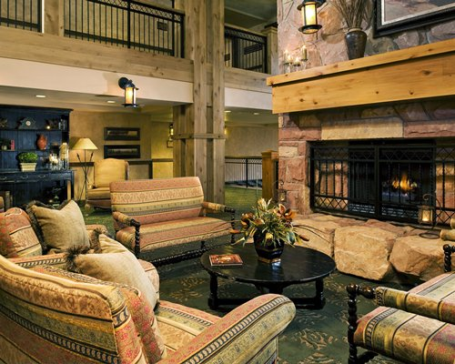 A well furnished living room with a fire in the fireplace and indoor balcony.