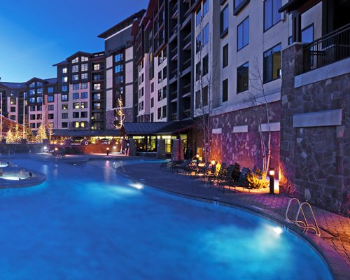 An outdoor swimming pool with chaise lounge chairs alongside the resort unit at night.