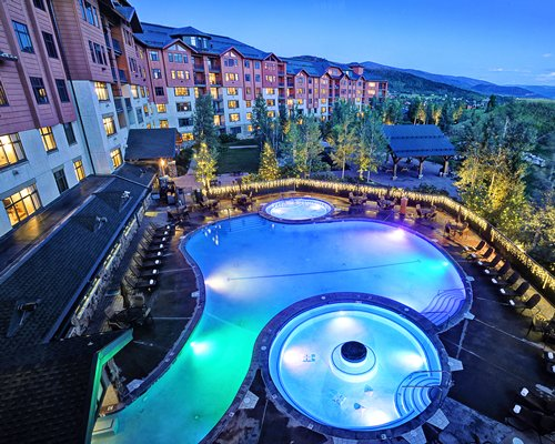 An outdoor swimming pool with hot tubs and chaise lounge chairs alongside multi story resort units at night.