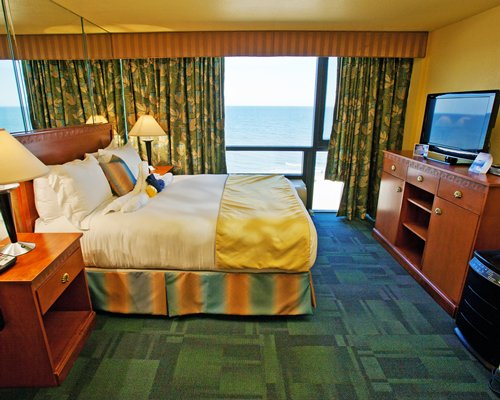 A well furnished bedroom with a television and the beach view.