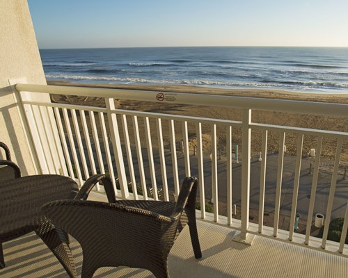 A balcony with patio furniture and beach view.