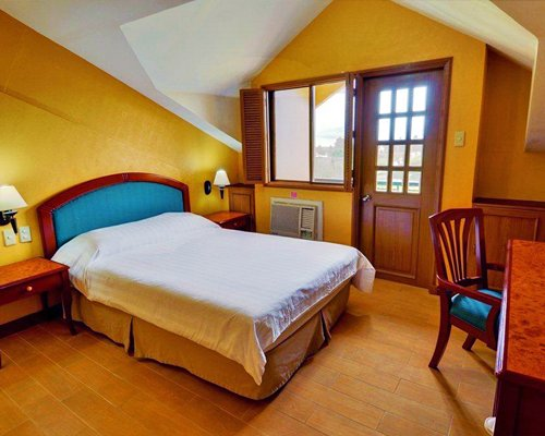 A well furnished bedroom with queen bed and outside view.