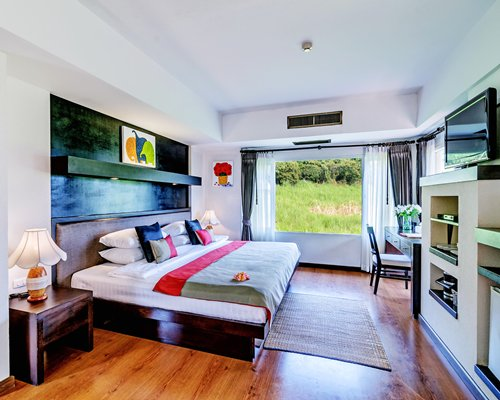A well furnished bedroom room with a television and an outside view.