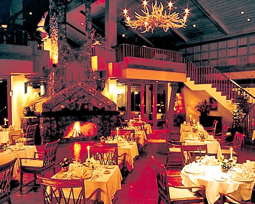 An indoor fine dining restaurant with fire at the fireplace alongside the staircase.