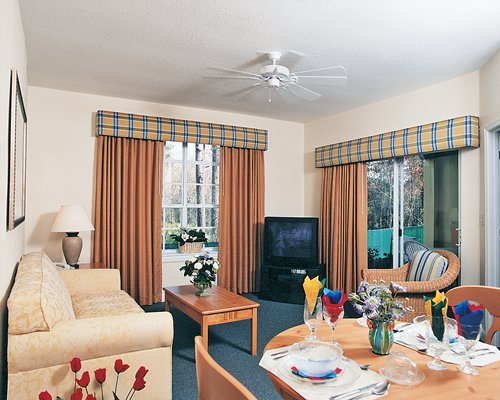 A well furnished living and dining area with a television and an outside view.