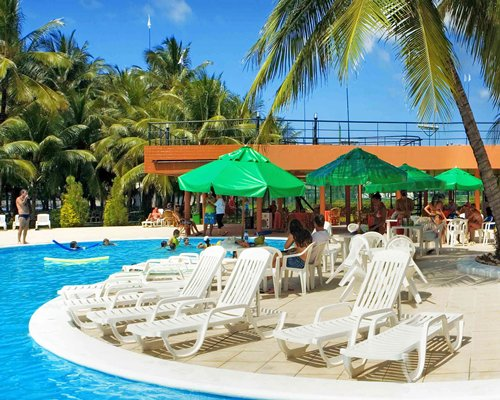 Outdoor swimming pool with chaise lounge chairs sunshades and palm trees.