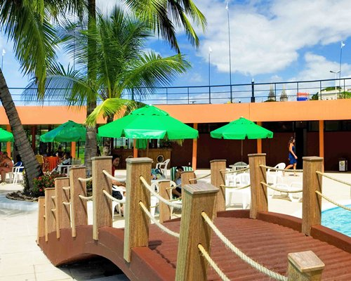 Bridge across an outdoor swimming pool with patio chairs sunshades and palm trees.