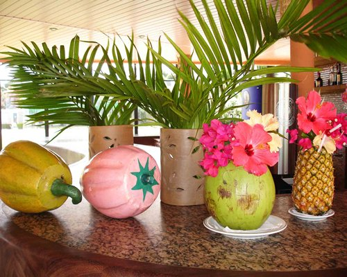 A coconut and pineapple decorated with flowers on a table.